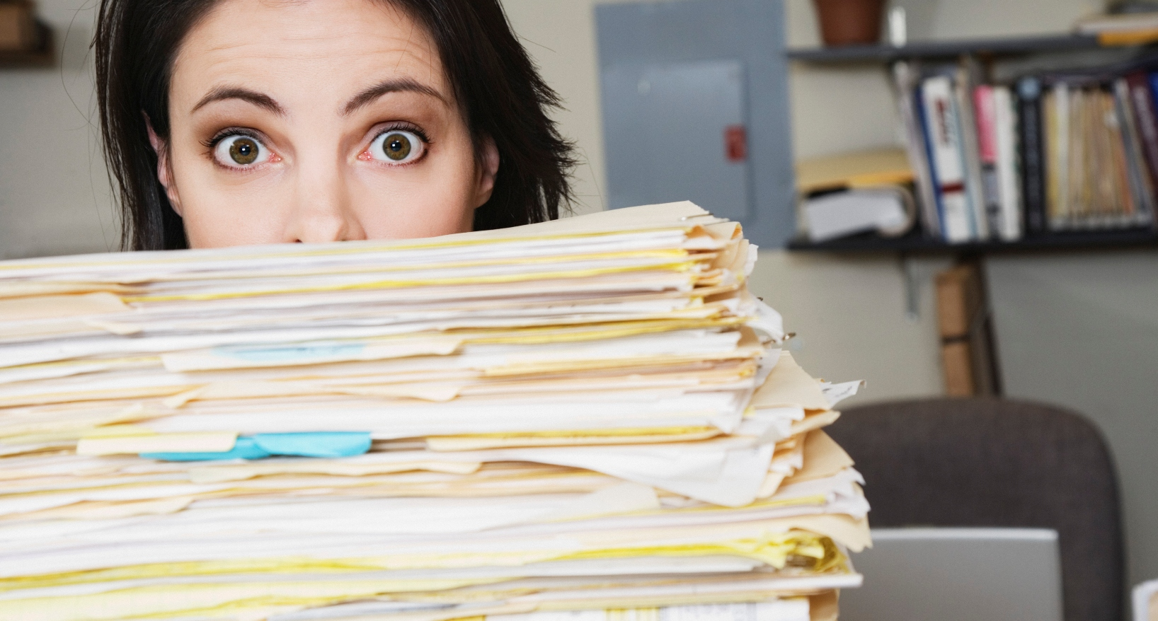 Surprised woman behind stack of files